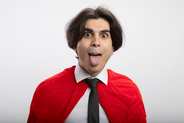 Joyful young superhero guy looking at camera wearing tie showing tongue isolated on white background