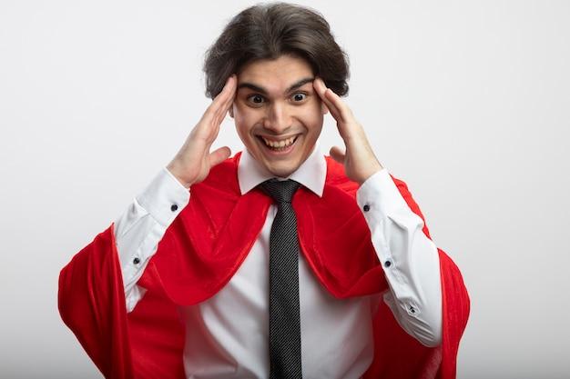 Радостный молодой парень супергероя смотрит вниз в галстуке и кладет пальцы на висок