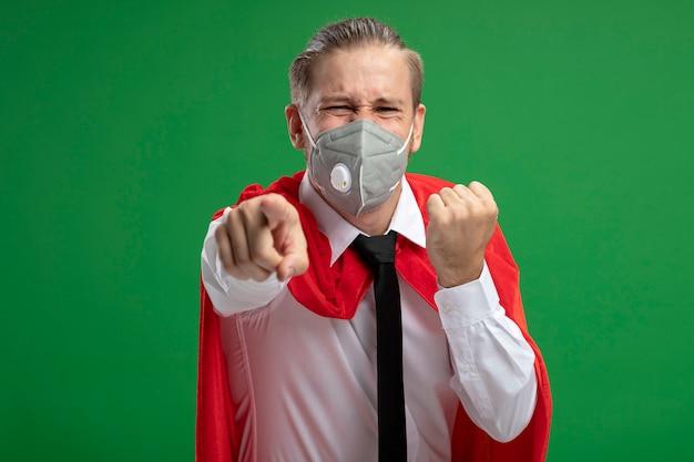 緑の背景に分離されたジェスチャーを示す医療マスクとネクタイを身に着けているうれしそうな若いスーパーヒーローの男