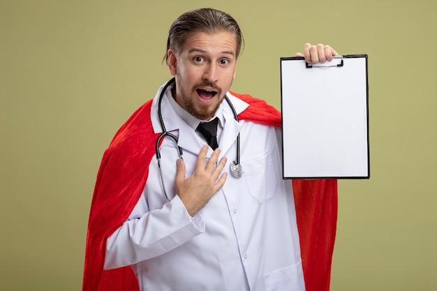 クリップボードを保持し、オリーブグリーンの背景で隔離の胸に手を置く医療ローブと聴診器を身に着けているうれしそうな若いスーパーヒーローの男