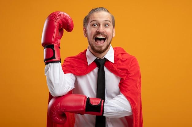 Gioioso giovane supereroe ragazzo indossa cravatta e guantoni da boxe alzando il pugno isolato sull'arancio
