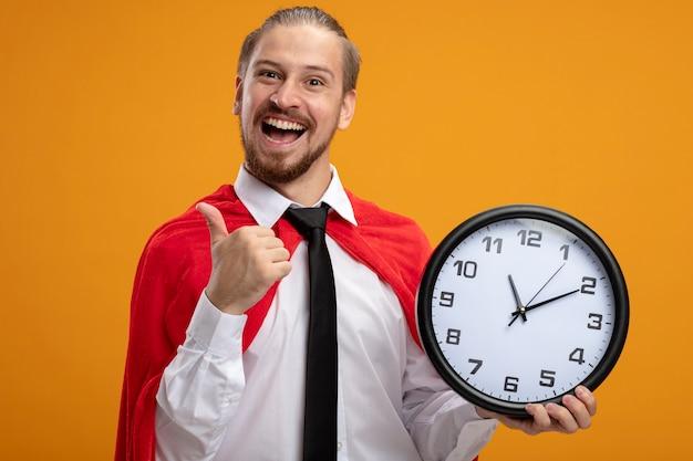 Радостный молодой супергерой в галстуке держит настенные часы и показывает палец вверх изолирован на оранжевом фоне
