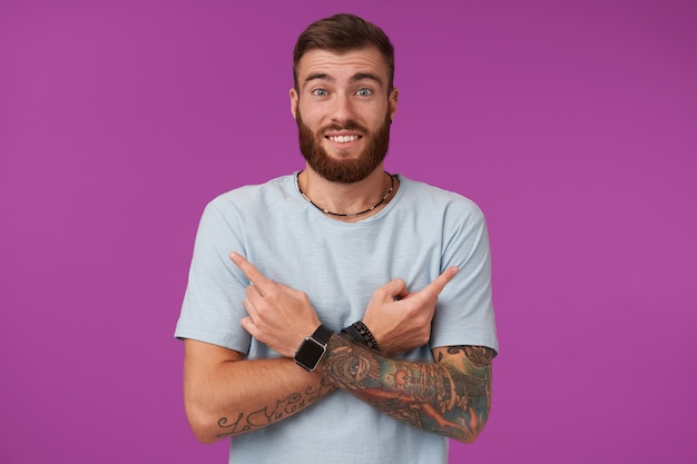 수염을 가진 즐거운 젊은 문신을 한 남자가 파란색 티셔츠를 입고 손을 가슴에 건 넜고 검지 손가락으로 다른면에 보이고 눈썹을 올리고 자주색으로 웃고 있습니다.