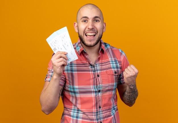Gioioso giovane viaggiatore che tiene in mano i biglietti aerei e tiene il pugno isolato sul muro arancione con spazio copia