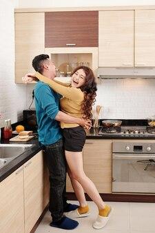 기념일 축하를 위해 저녁을 요리할 때 부엌에서 껴안고 춤을 추는 즐거운 젊은 베트남 부부