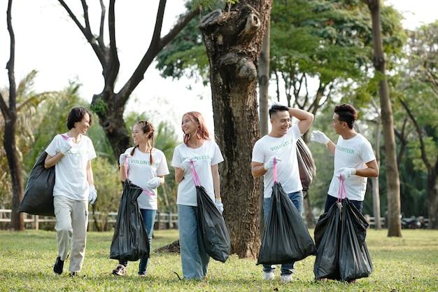 공원을 청소하고 쓰레기를 주울 때 비닐 봉지를 들고 즐거운 젊은 자원 봉사자