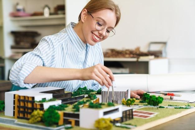 Радостная молодая женщина-архитектор в очках, проектирующая проект с моделью дома и сидя на рабочем месте