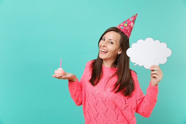 Joyful young woman in birthday hat hold in hand cake with candle empty blank say cloud, speech bubble for promotional content isolated on blue background. people lifestyle concept. mock up copy space.