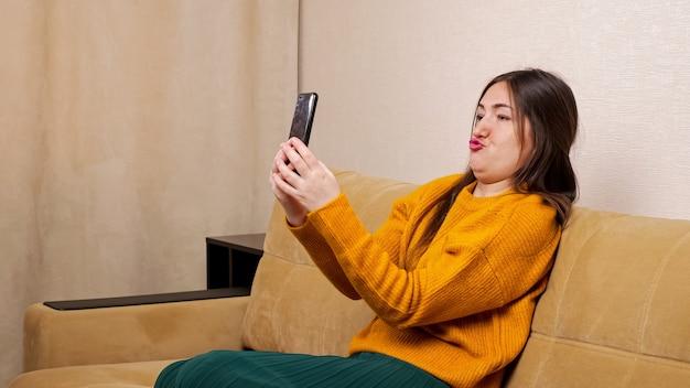 길고 느슨한 머리를 가진 즐거운 젊은 여성 블로거는 갈색 소파에 앉아 집에서 슬로우 모션으로 찡그린 검은색 스마트폰을 들여다봅니다.