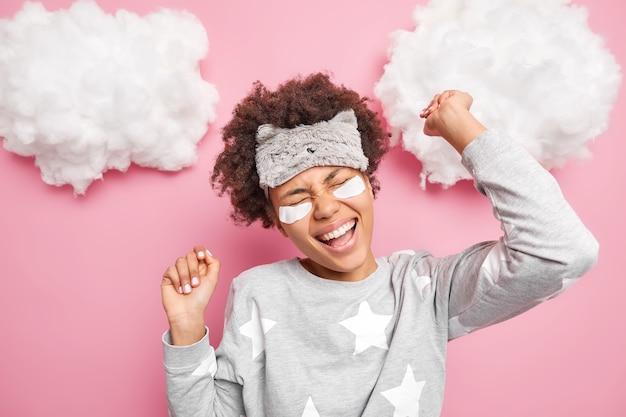 うれしそうな若い女性が気楽に踊り、腕を上げて笑顔を広げ、ピンクの壁に隔離されたナイトウェアを着た目の下にコラーゲンパッチを広く適用