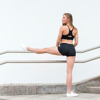 Радостная молодая женщина делает упражнения длинный выстрел