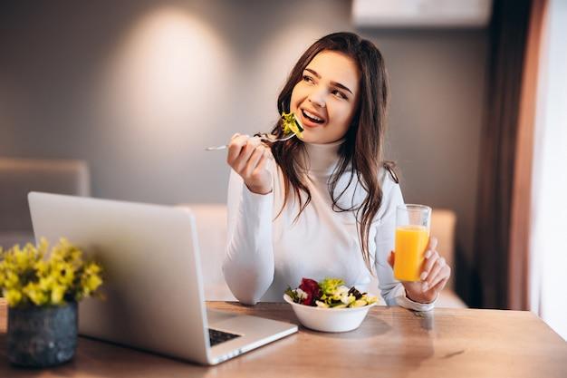 オレンジジュースを飲みながら、キッチンに立ってノートパソコンで映画を見ながら、ボウルからサラダを食べるのを楽しんでいるうれしそうな若い女性。