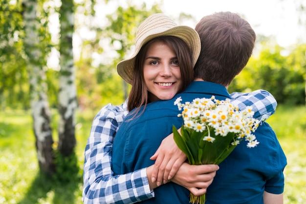 うれしそうな若い女性が公園で彼氏を抱きしめる