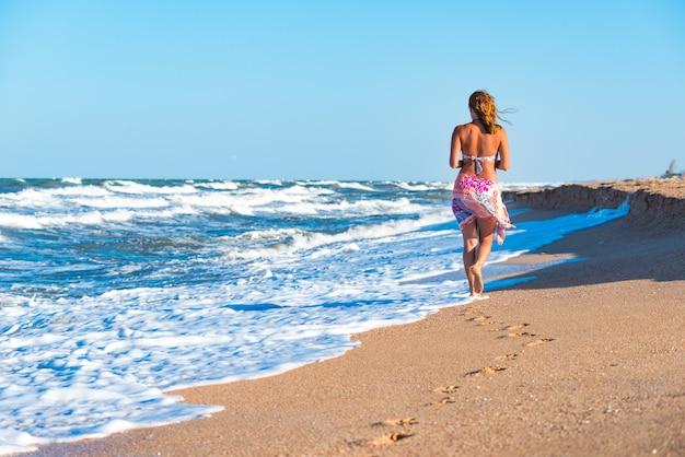 うれしそうな若い女性は、地平線をはるかに超えて見ている海の嵐の波を楽しんでいます