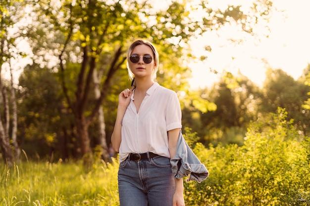 Gioiosa giovane donna con occhiali da sole alla moda che cammina nella natura in una bella giornata
