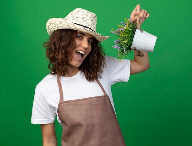 緑に分離された植木鉢の花を保持しているガーデニング帽子を身に着けている制服を着たうれしそうな若い女性の庭師