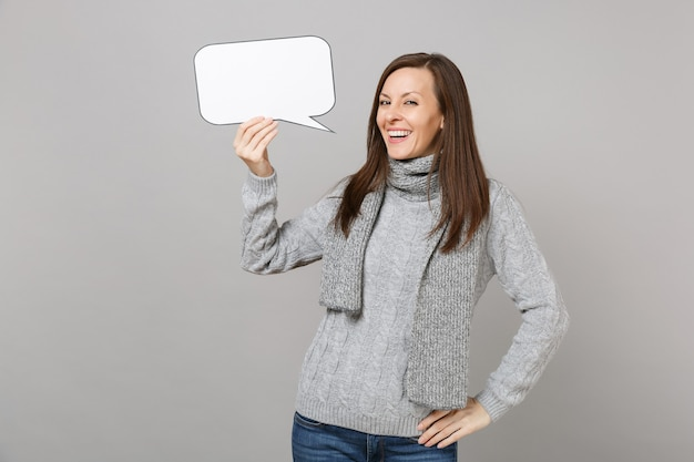 Joyful young woman in gray sweater, scarf holding empty blank say cloud, speech bubble isolated on grey background. healthy fashion lifestyle, people emotions, cold season concept. mock up copy space.