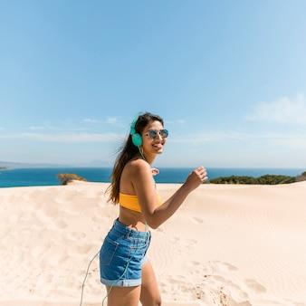 Joyful young woman in headphones on seaside
