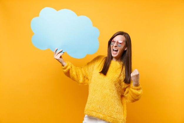 Joyful young woman in heart eyeglasses hold empty blank blue say cloud speech bubble doing winner gesture screaming isolated on yellow background. people sincere emotions, lifestyle. advertising area.