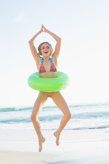 해변에서 점프 고무 링을 들고 즐거운 젊은 여자