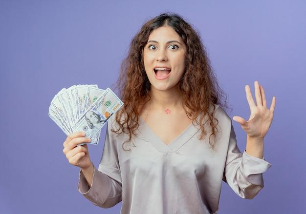 現金を保持し、青で隔離の手を広げて楽しい若い女性