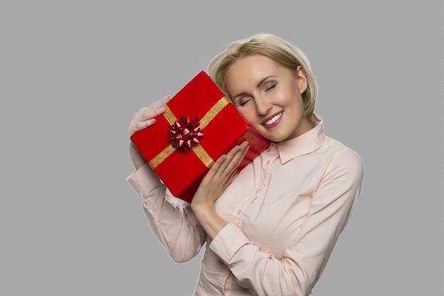 회색 바탕에 선물 상자를 들고 즐거운 젊은 여자. 빨간 선물 상자와 함께 포즈를 취하는 예쁜 소녀. 가까운 사람으로부터의 아름다운 선물.