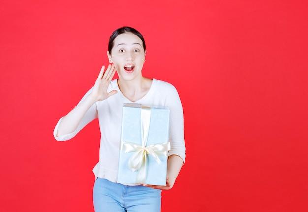 Gioiosa giovane donna che tiene in mano una confezione regalo e dice qualcosa