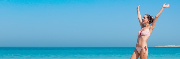 Радостная молодая женщина в купальнике с поднятыми руками у стены моря