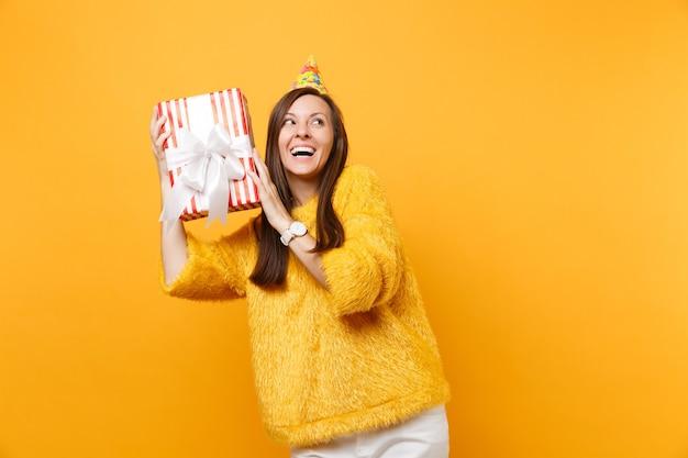 明るい黄色の背景で隔離の休日を楽しんで祝うギフトプレゼントと赤い箱に何が入っているかを推測しようと見上げる誕生日の帽子をかぶったうれしそうな若い女性。人々は誠実な感情、ライフスタイル。