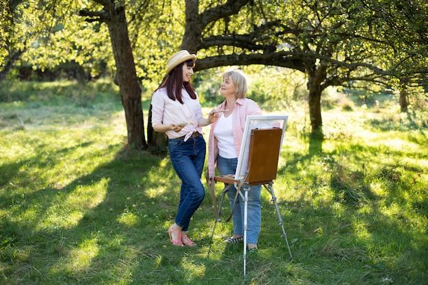 カジュアルな服装と麦わら帽子をかぶったうれしそうな若い女性が、庭で屋外で楽しみ、成熟した母親と一緒に絵を描いている.共同活動、創造性のコンセプト。