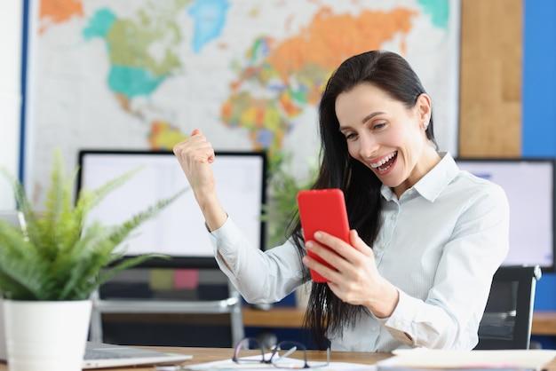 陶酔感のあるうれしそうな若い女性がスマートフォンの画面を見る