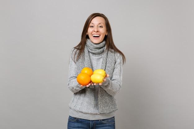 Радостная молодая женщина в сером свитере, шарфе держит лимоны, апельсины, изолированные на сером фоне студийный портрет. здоровый образ жизни моды, искренние эмоции людей, концепция холодного сезона. копируйте пространство для копирования.