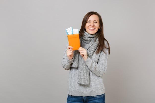 회색 스웨터를 입은 즐거운 젊은 여성, 회색 배경에 격리된 여권 탑승권을 들고 스카프. 건강한 패션 라이프스타일 사람들은 진심 어린 감정, 추운 계절 개념입니다. 복사 공간을 비웃습니다.