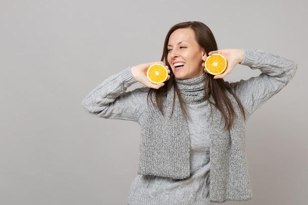 Радостная молодая женщина в сером свитере, шарфе, смотрящем в сторону апельсинов владения изолированными на сером фоне в студии. здоровый образ жизни моды, искренние эмоции людей, концепция холодного сезона. копируйте пространство для копирования.