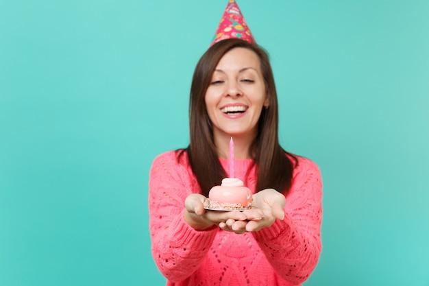 파란색 청록색 벽 배경 스튜디오 초상화에 격리된 촛불과 함께 손 케이크를 들고 있는 분홍색 스웨터와 생일 모자를 쓴 즐거운 젊은 여성. 사람들이 라이프 스타일 개념입니다. 복사 공간을 비웃습니다.