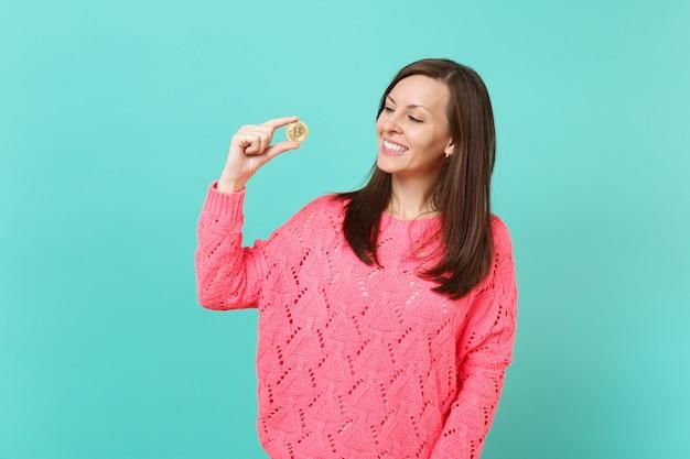 분홍색 스웨터를 입은 즐거운 젊은 여성이 파란색 청록색 벽 배경, 스튜디오 초상화에 격리된 미래 통화인 비트코인을 바라보며 손을 잡고 있습니다. 사람들이 라이프 스타일 개념입니다. 복사 공간을 비웃습니다.