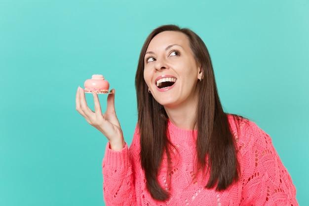 Радостная молодая женщина в вязаном розовом свитере, глядя вверх, держа в руке торт, изолированный на синем фоне бирюзовой стены, студийный портрет. люди искренние эмоции, концепция образа жизни. копируйте пространство для копирования.