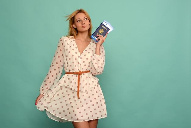 Радостная молодая женщина в платье в горошек держит авиабилеты с паспортом на синем фоне.