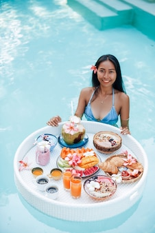 トロピカルな食べ物でいっぱいのフローティングテーブルと水着のうれしそうな若い女性は、豪華なホテルのプールで泳ぎます。