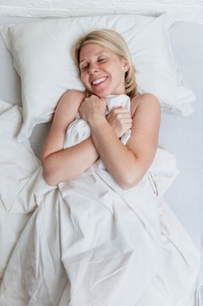 Радостная молодая женщина лежит в постели. полный сон и расслабление.