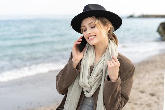 うれしそうな若い女性がスタイリッシュな服を着てビーチで完璧な笑顔で携帯電話で話している