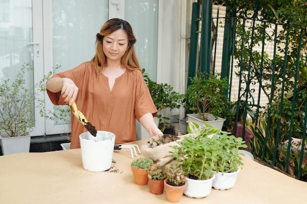 Радостная молодая женщина сажает цветы в горшках за столом на заднем дворе своего дома