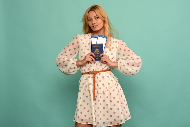Joyful young woman in polka dot dress is holding airline tickets with a passport on a blue background.