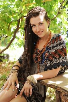 Радостный портрет молодой женщины с дредами, одетый в платье в стиле бохо и ожерелье