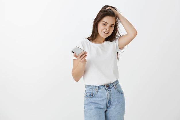 Радостная молодая женщина позирует со своим телефоном и наушниками на белой стене