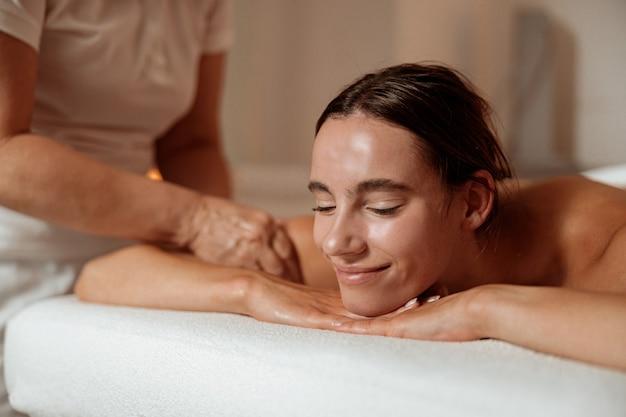 Joyful young woman receiving professional massage in spa salon