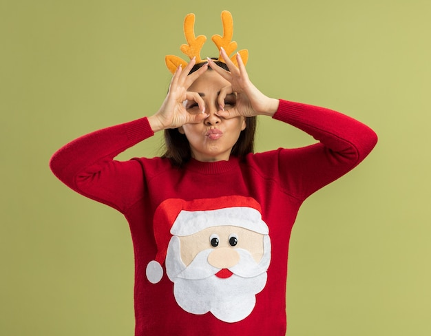 Joyful young woman in  red christmas sweater wearing funny rim with deer horns  through fingers making binocular gesture standing over green wall