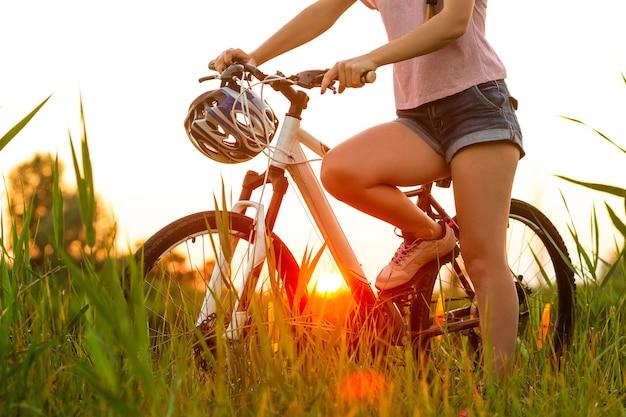 川沿いと牧草地の遊歩道で自転車に乗ってうれしそうな若い女性