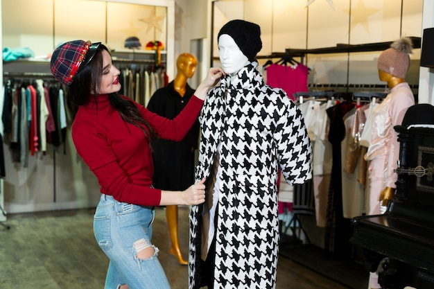 Радостная молодая женщина покупает теплые куртки в магазине одежды.