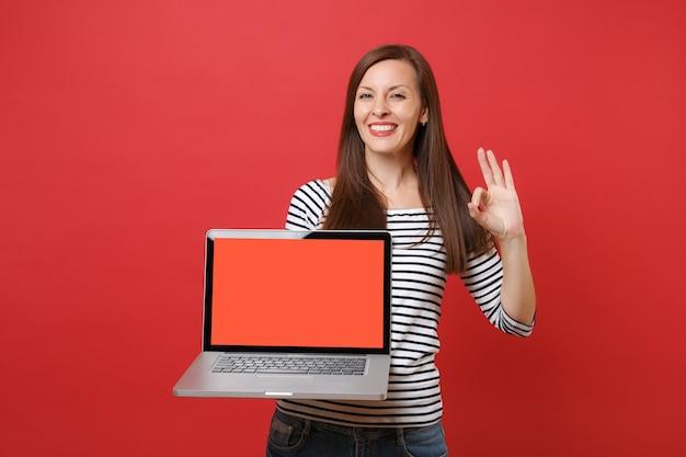 明るい赤の壁の背景に分離された空白の黒い空の画面でラップトップpcコンピューターを保持し、okサインを示すうれしそうな若い女性。人々の誠実な感情、ライフスタイルのコンセプト。コピースペースをモックアップします。
